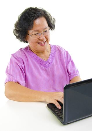 Asian senior woman using notebook over white background photo