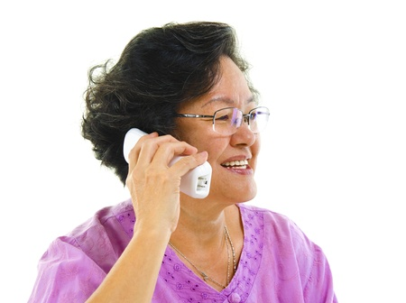 Happy mature Asian woman talking on phone, isolated on white background photo