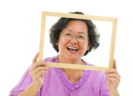 Smiling old Asian woman looking through an empty frame, isolated on white background photo