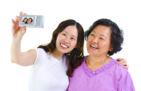 Asian girl and senior mother self photographing, isolated on white