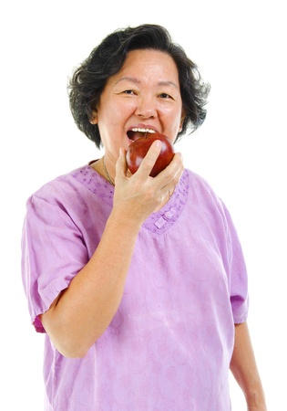 Healthy lifestyle concept. Asian senior woman eating an apple over white background photo