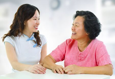 Asian family, adult daughter having conversation with senior mother indoor. photo
