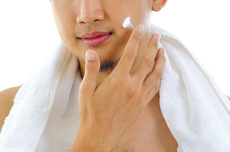 Asian man putting on cream lotion on face photo