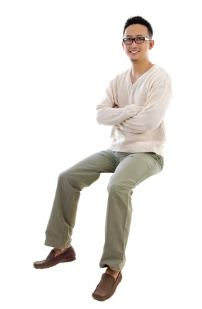 Full body Asian man sitting on a transparent block over white background photo