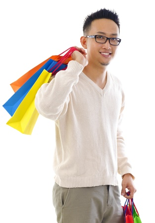 Happy Asian man shopper holding shopping bag over white background photo