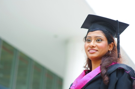 Smiling young Indian female graduate looking away photo