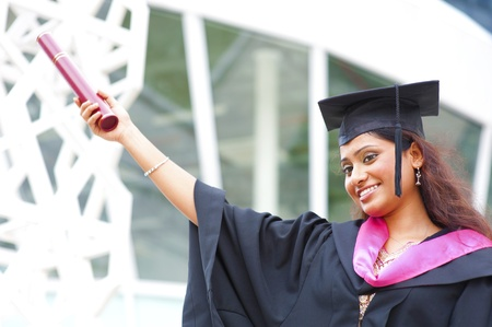 Happy young Indian in a graduation gown and cap holding her diploma photo