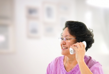 Happy mature Asian woman talking on phone, inside house photo