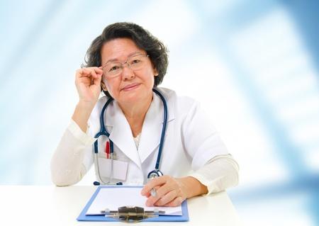 Asian senior female doctor sitting inside hospital room photo