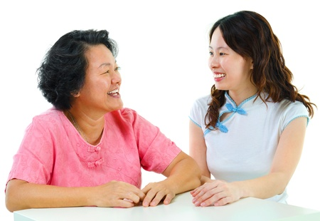 Adult daughter having conversation with senior mother indoor. photo