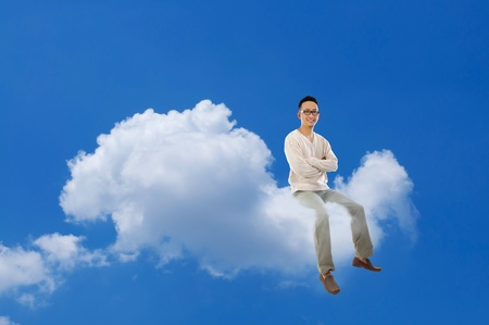 Full body Asian man sitting on a cloud over blue sky photo