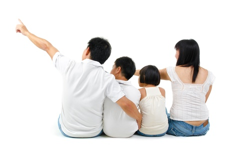 Rear view of Asian family looking at side, sitting on white background photo