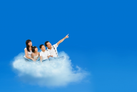 Happy Asian family sitting on cloud and pointing over blue sky photo