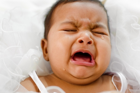 Crying Indian baby girl lying on bed photo