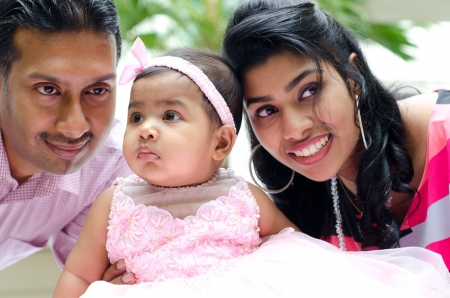 Indian parents and baby girl at outdoor home garden photo