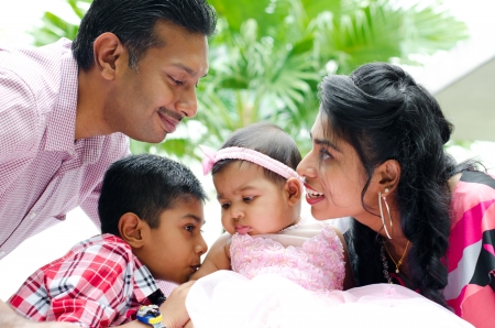 Happy Indian family with two children having fun at home garden photo