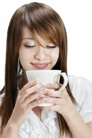 woman drinking tea: Asian female holding a cup over white background