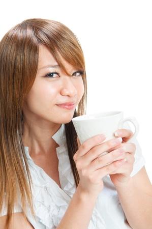 tomando refresco: Hermosa joven asi�tica que sostiene una taza de t�  caf� sobre fondo blanco