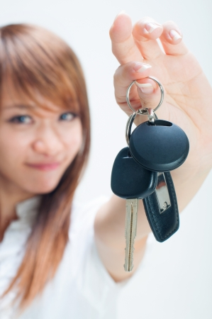 new driver: Young woman holding her first own car key on white background, focus on car key. Stock Photo