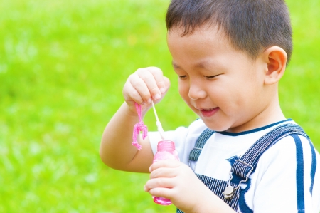 candid: Asian boy blowing bubbles outdoor Stock Photo