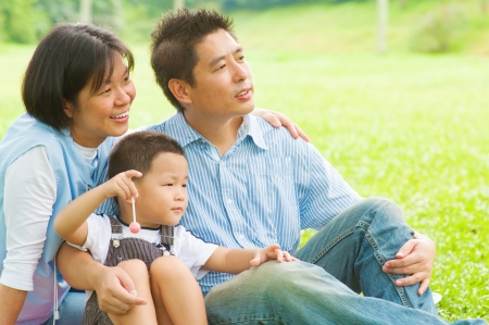Happy Asian family having fun at outdoor park photo