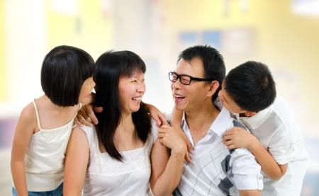 padres hablando con hijos: Familia asi�tica feliz compartiendo su historia dentro de la casa