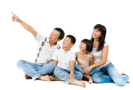 Happy Asian family sitting on floor and pointing over white background photo