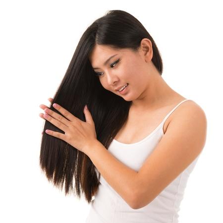tratamiento capilar: Hermosa mujer asi�tica que aplica la crema del pelo, aislados en fondo blanco