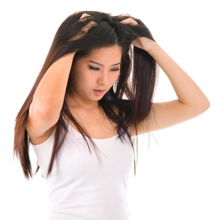 annoying: Young Asian girl scratches her hair on white background