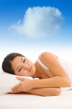 Young Asian girl sleeping on a pillow with white cloud over her top photo
