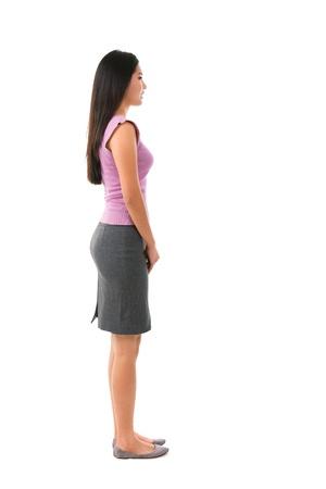 persona de pie: Vista lateral de todo el cuerpo de la hembra asi�tica en traje de oficina de pie sobre fondo blanco Foto de archivo