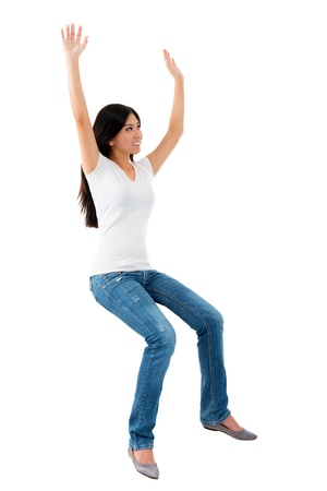 whole body: Excited young Asian girl raise her hands up, sitting on invisible chair over white background