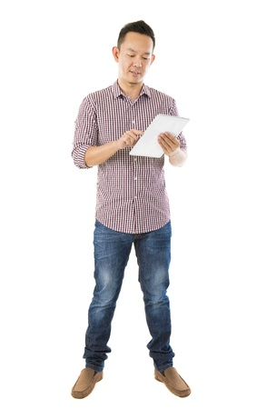 the whole body: Fullbody Asian man using tablet computer standing over white background Stock Photo
