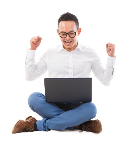 Excited Asian man using laptop on the floor over white background photo