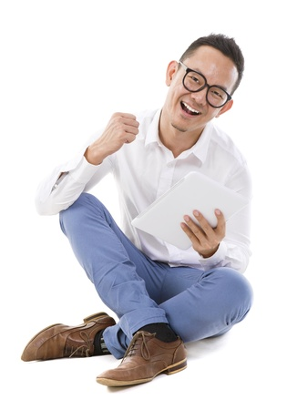 the whole body: Fullbody happy Asian man sitting on floor using tablet computer Stock Photo