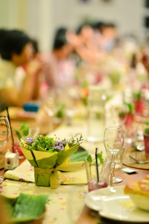 Reunion party in warm ambient , focus on the flower bouquet on dining table. photo