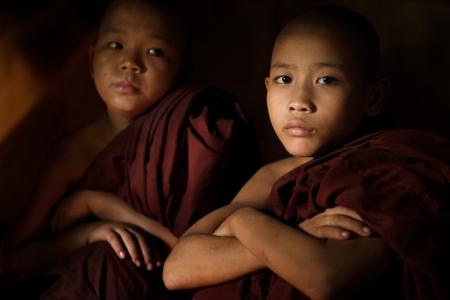 birma: Jonge boeddhistische monnik novice in een tempel achtergrond, weinig licht instelling