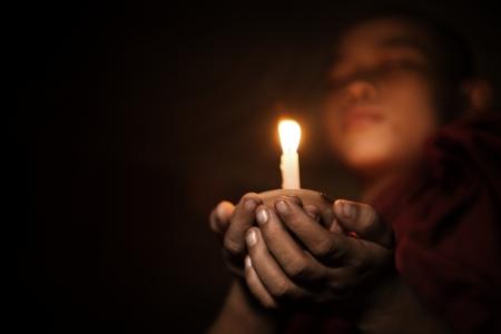 luz de vela: Monje novicio joven que sostiene una vela