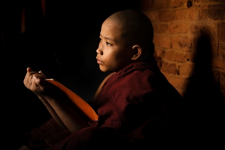 Young novice monk learning inside monastery