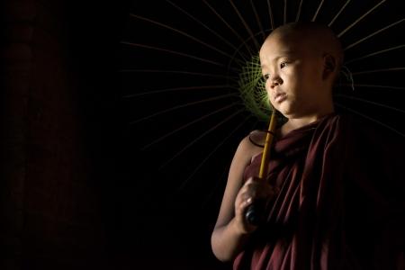 A Young novice monk holding an umbrella photo