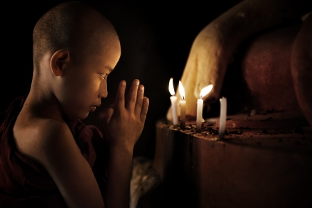 Little novice monk praying in front candlelight photo