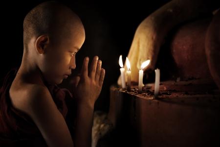 Myanmar: Moine novice peu prier � la bougie avant Banque d'images