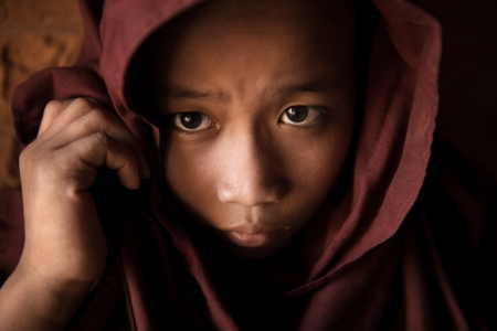 poor people: A young novice monk covered his head by robe