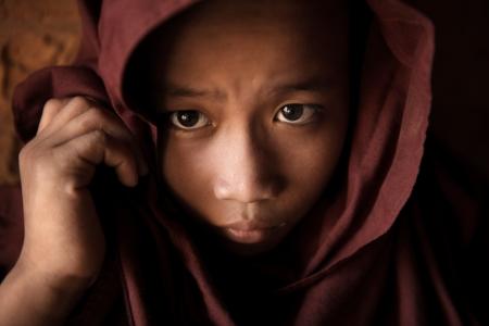 birma: Een jonge novice monnik bedekte zijn hoofd met mantel