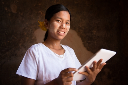 Happy Myanmar girl with her new digital tablet computer Stock Photo - 16118491