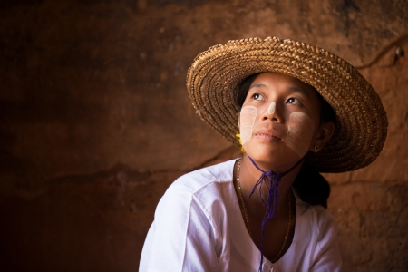Traditional Myanmar girl in straw hot is looking away photo