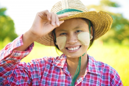 Portrait of a young Burmese woman with thanaka powdered face who works in the field photo