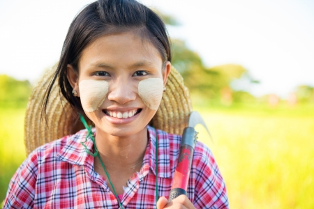Portrait of a Burmese girl with thanaka powdered face who works in the field photo