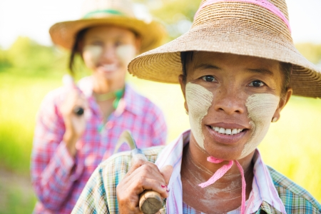 Portrait of a two Myanmar farmer with thanaka powdered face who works in the field photo