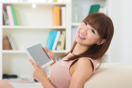 bookshelves: Happy Asian girl using tablet computer indoor Stock Photo